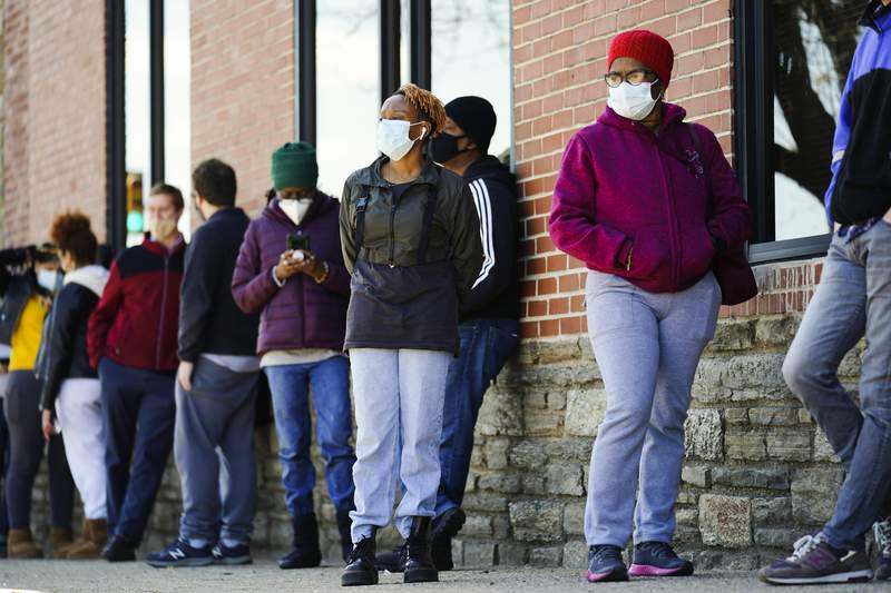 FILE - In this March 29, 2021, file photo, people wearing face masks as a precaution against the coronavirus wait in line to receive COVID-19 vaccines at a site in Philadelphia. (AP Photo/Matt Rourke, File)