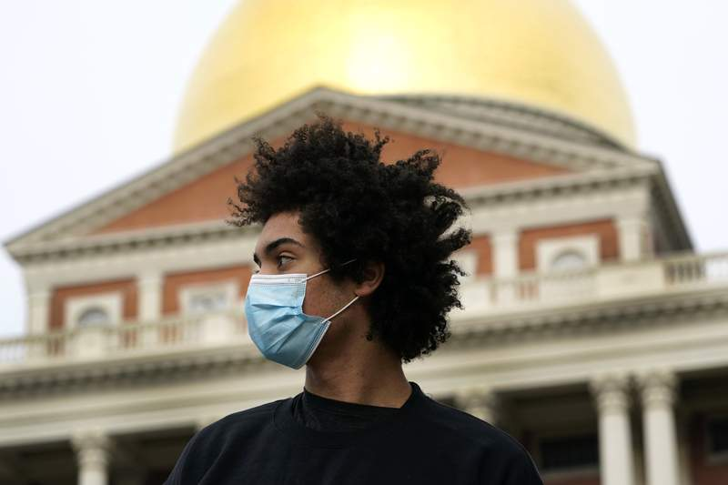 """Isaac Smith, of Boston, speaks to a reporter near the Massachusetts Statehouse in Boston about the new incoming administration, Wednesday, Jan. 20, 2021. Smith, a 21-year-old Harvard University student, said he voted for Biden and was excited for what's to come. """"No matter which way you look at it, it's historic. Things are going to change,"""" he said. (AP Photo/Elise Amendola)"""