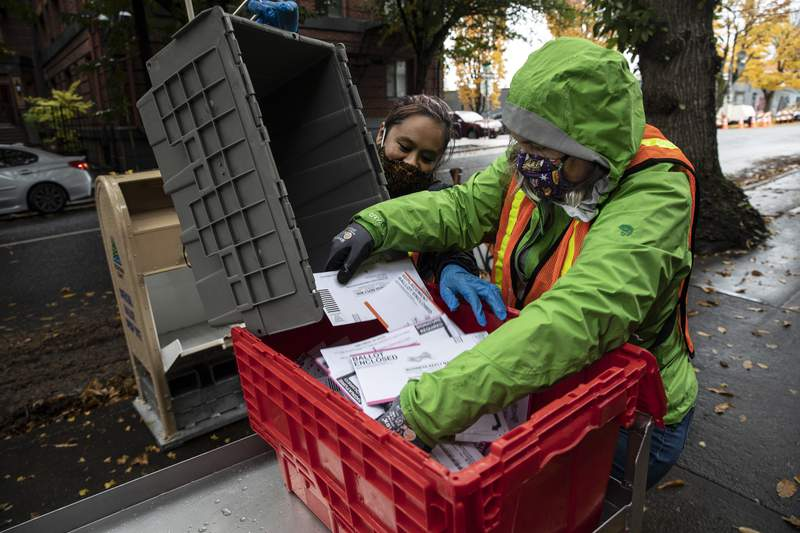 Election workers empty ballots from a ballot dropbox to the Multnomah County Election headquarters Tuesday, Nov. 3, 3030 in Portland, Ore. Oregon is the first state in the nation to institute voting by mail and automatic voter registration. (AP Photo/Paula Bronstein)