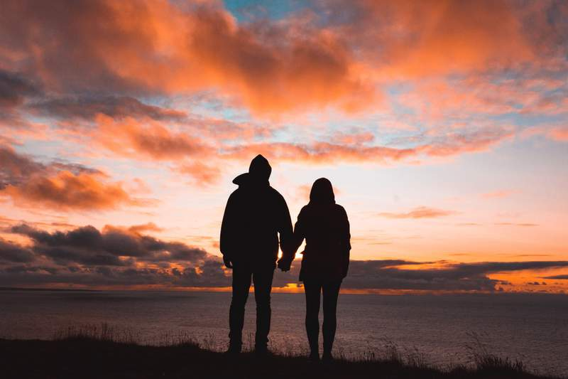 Love is holding hands at the lakeshore, watching the sunset