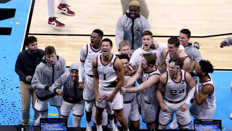 Jalen Suggs #1 of the Gonzaga Bulldogs celebrates with teammates after making a game-winning three point basket in overtime to defeat the UCLA Bruins 93-90. (Photo by Andy Lyons)