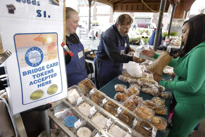 FILE - In a Sept. 11, 2010, file photo, Temeka Williams, right, of Detroit, uses her bridge card tokens for a purchase from Elizabeth and Gary Lauber from Sweet Delights at the Farmer's Market in Detroit. (AP Photo/Carlos Osorio, File)