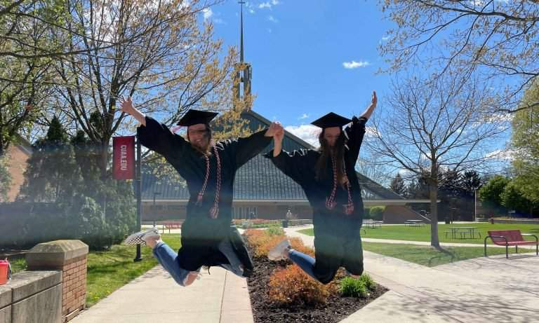 Graduates jump for a photo on Central Campus, in front of The Chapel of the Holy Trinity.