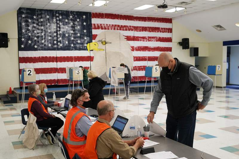 A voter check with the registration table as he prepares to cast his ballots under a giant mural at Robious Elementary school on Election Day, in Midlothian, Va., Tuesday Oct. 3, 2020. Poll workers said that traffic was slow due to all the early voting in the precinct. (AP Photo/Steve Helber)