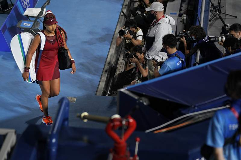 Naomi Osaka, of Japan, leaves center court after being defeated by Marketa Vondrousova, of the Czech Republic, during the third round of the tennis competition at the 2020 Summer Olympics, Tuesday, July 27, 2021, in Tokyo, Japan. (AP Photo/Seth Wenig)