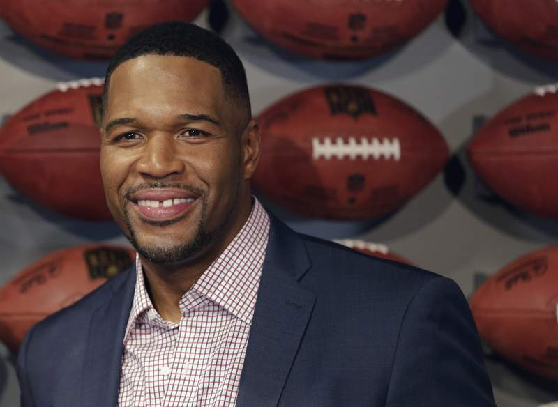 """FILE - In this Thursday, Nov. 30, 2017 file photo, Former New York Giant Michael Strahan poses for a picture at the opening of """"NFL Experience"""" in Times Square, New York. Pro Football Hall of Famer and Good Morning America host Michael Strahan has tested positive for COVID-19 and is self-quarantining, according to people familiar with the situation. They spoke to The Associated Press on condition of anonymity Wednesday, Jan. 27, 2021 because of medical restriction issues. (AP Photo/Seth Wenig, File)"""