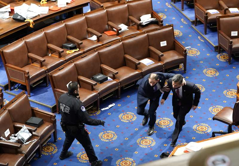 Members of congress run for cover as protesters try to enter the House Chamber during a joint session of Congress on January 06, 2021 in Washington, DC. Congress held a joint session today to ratify President-elect Joe Biden's 306-232 Electoral College win over President Donald Trump. A group of Republican senators said they would reject the Electoral College votes of several states unless Congress appointed a commission to audit the election results. (Photo by Drew Angerer/Getty Images)