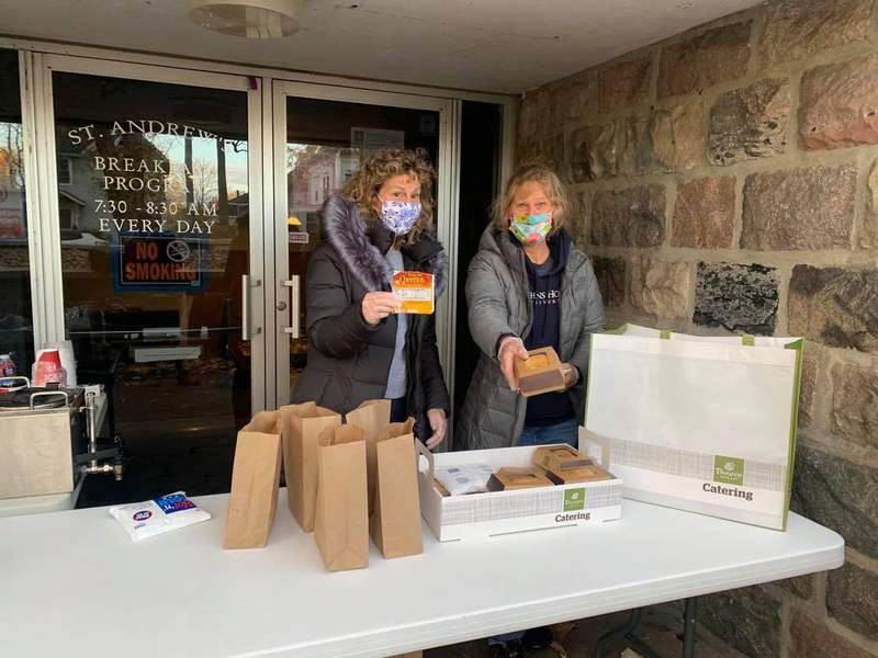 Volunteers Ann and Melanie hand out breakfasts to go.