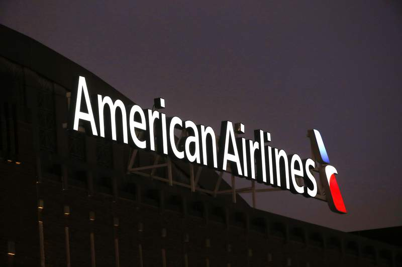 This Dec. 19, 2017, photo shows the American Airlines logo on top of the American Airlines Center in Dallas. The longest-running in-flight magazine on a major airline is nearing its final flight. American Airlines says it is dropping the American Way magazine, Friday, June 11, 2021,  after a 55-year run.   (AP Photo/ Michael Ainsworth, File)