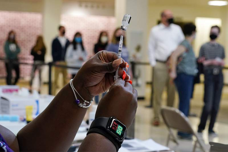 Licensed practical nurse Adrian McCain prepares a Pfizer COVID-19 vaccination at a Montgomery County Office of Public Health vaccination clinic at the King of Prussia Mall, Tuesday, May 11, 2021, in King of Prussia, Pa.,  (AP Photo/Matt Slocum)