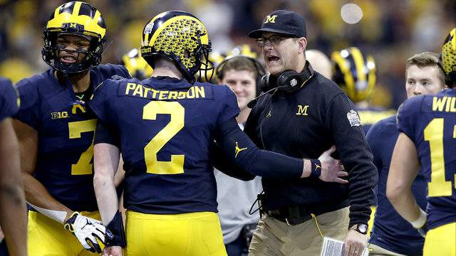 Shea Patterson #2 and head coach Jim Harbaugh of the Michigan Wolverines celebrate the first quarter touchdown against the Florida Gators during the Chick-fil-A Peach Bowl at Mercedes-Benz Stadium on December 29, 2018 in Atlanta, Georgia. (Photo by Joe Robbins/Getty Images)