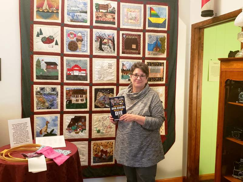 """Ann Arbor author Patricia Majher with her latest book, """"100 Things To Do in Ann Arbor Before You Die,"""" in front of a handmade quilt at the Hamburg Township Historical Museum."""