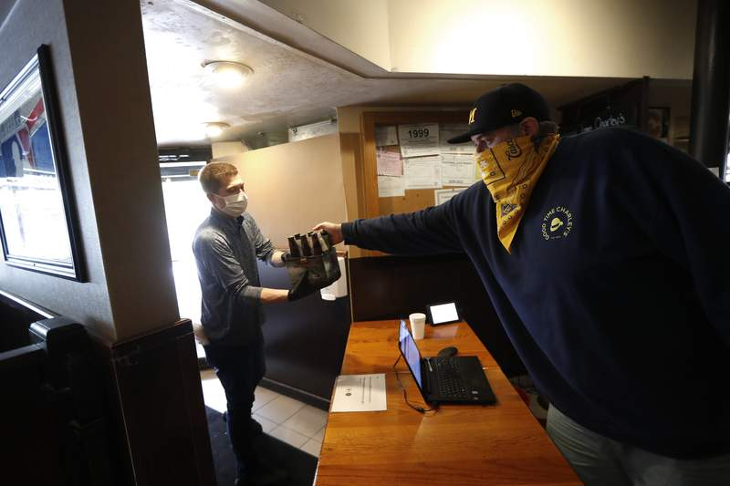 In this May 19, 2020, photo, Kyle Froelich, right, hands a customer a carryout six-pack of beer at Good Time Charley's in Ann Arbor, Mich. Michigan restaurants and bars could sell cocktails and liquor for pickup or delivery and would see a temporary cut in state liquor prices under fast-tracked legislation that supporters hope will help the industry survive the coronavirus pandemic. The state already lets bars and restaurants sell unopened beer and wine to go. (AP Photo/Paul Sancya)
