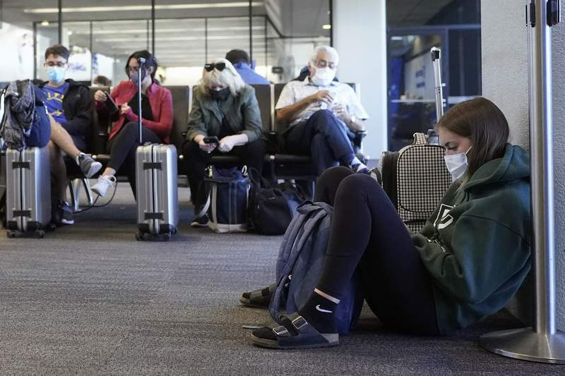 Passenger Cari Driggs, right, from Provo, Utah, waits to board a United Airlines flight to Hawaii for vacation at San Francisco International Airport in San Francisco, Thursday, Oct. 15, 2020. (AP Photo/Jeff Chiu)