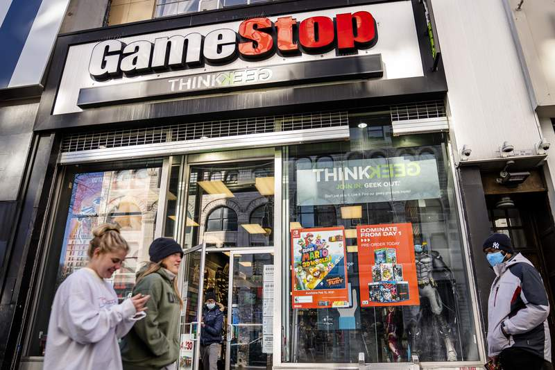 FILE - In this Jan. 28, 2021, file photo, pedestrians pass a GameStop store on 14th Street at Union Square, in the Manhattan borough of New York. The recent GameStop frenzy provided what parents and educators call a teachable moment - an opportunity that presents itself to lend a little insight. The Associated Press talked to a few parents and financial experts for their tips, and included in their advice was teaching kids early on about money, keeping the discussions simple but interesting and letting kids practice investing. (AP Photo/John Minchillo, File)
