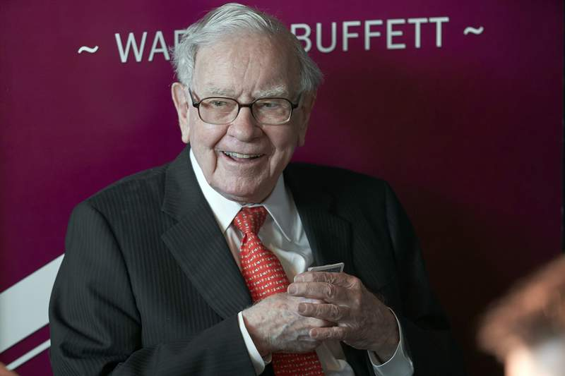 FILE - In this May 5, 2019, file photo Warren Buffett, Chairman and CEO of Berkshire Hathaway, smiles as he plays bridge following the annual Berkshire Hathaway shareholders meeting in Omaha, Neb. Buffett's company pared back its holdings in financial firms further during the first quarter and also halved its new investment in Chevron. Berkshire Hathaway Inc. provided an update on its U.S. stock holdings in a filing with regulators Monday, May 17, 2021. Many investors follow Berkshire's holdings closely because of Buffett's remarkably successful record. (AP Photo/Nati Harnik, File)