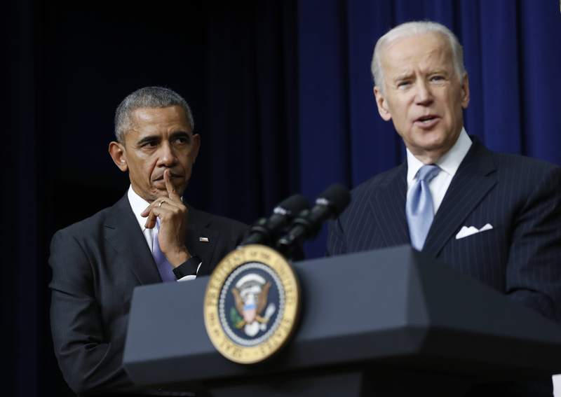 FILE - In this Dec. 13, 2016, file photo, President Barack Obama listens as Vice President Joe Biden speaks in the South Court Auditorium in the Eisenhower Executive Office Building on the White House complex in Washington. Biden is getting some help from Obama as he looks to fill his campaign coffers and unify the Democratic party ahead of the November election. Obama and Biden will appear together Tuesday, June 23, for a virtual grassroots fundraiser, the former vice president announced on Twitter. (AP Photo/Carolyn Kaster, File)