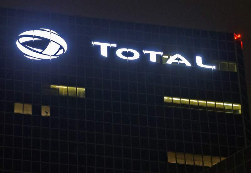 FILE - In this Oct. 12, 2016, file photo, the logo of French oil giant Total SA is pictured at company headquarters in La Defense business district, outside Paris. French energy giant Total signed mega contracts with Iraq worth $27 billion to develop oil fields, natural gas and a crucial water project that officials said Monday, Sept. 6, 2021, will be key for the oil-rich country to maintain crude output. (AP Photo/Michel Euler, File)