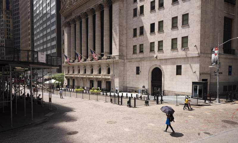 FILE - People pass the New York Stock Exchange, Thursday, July 30, 2020.  Wall Street is stalling on Friday, Aug. 7 as a whirlwind of worries about rising U.S-China tensions and whether Congress can deliver more aid for the economy threaten to halt its big run.(AP Photo/Mark Lennihan)
