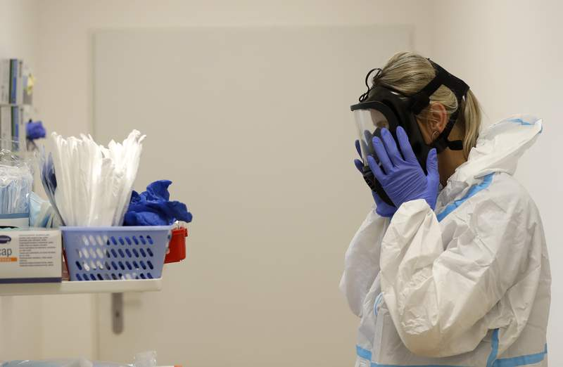 A health care worker puts on personal protective equipment before tending to COVID-19 patients at an intensive care unit. (AP Photo/Petr David Josek)