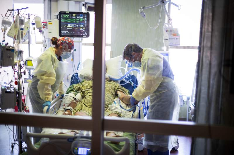"""FILE - In this Aug. 31, 2021, file photo, Dr. William Dittrich M.D. looks over a COVID-19 patient in the Medical Intensive care unit (MICU) at St. Luke's Boise Medical Center in Boise, Idaho. An advocacy group for seniors has filed a civil rights complaint against Idaho over the state's """"crisis standards of care"""" guidelines for hospitals overwhelmed during the coronavirus pandemic. Justice in Aging wants the U.S. Department of Health and Human Services to investigate Idaho's health care rationing plan, contending that it discriminates against older adults by using factors like age in prioritizing which patients may get access to life-saving care. (AP Photo/Kyle Green, File)"""