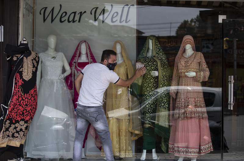 A Kashmiri shopkeeper cleans the display of his shop that was opened following a partial relaxation in the lockdown imposed to curb the spread of coronavirus in Srinagar, Indian controlled Kashmir, Monday, May 31, 2021. (AP Photo/Mukhtar khan)