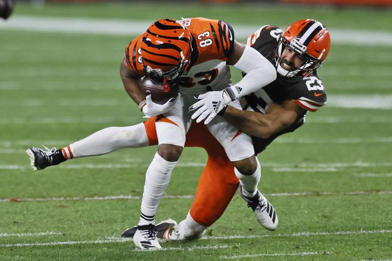 FILE - In this Thursday, Sept. 17, 2020 file photo, Cleveland Browns strong safety Andrew Sendejo (23) tackles Cincinnati Bengals wide receiver Tyler Boyd (83) after a pass reception during the second half of an NFL football game in Cleveland. The Cleveland Browns added starting safety Andrew Sendejo and rookie tight end Harrison Bryant to their lengthy COVID-19 list, Tuesday, Dec. 29, 2020. (AP Photo/Ron Schwane, File)