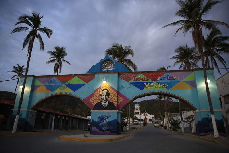 FILE - In this March 17, 2019 file photo, a mural of Nelson Mandela, who spent many of his imprisoned years in an island prison in South Africa, adorns a gate in front of the dock where prison staff and inmates arrive in Navy boats to the now closed Islas Maria penal colony located off Mexico's Pacific coast. Mexican officials said on Saturday, March 13, 2021, that ferries and cruise ships may soon be visiting the former prison, after the last island penal colony in the Americas was closed and turned into an environmental education center in 2019.  (AP Photo/Rebecca Blackwell, File)