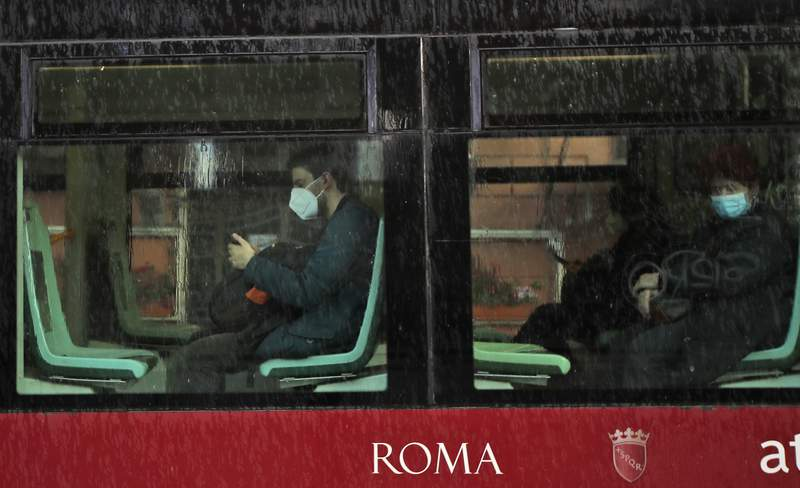 People wearing face masks to curb the spread of COVID-19, sit at distance in a tram in downtown Rome, Monday, March 15, 2021. Half of Italy's regions have gone into the strictest form of lockdown in a bid to curb the latest spike in coronavirus infections that have brought COVID-19 hospital admissions beyond manageable thresholds.(AP Photo/Alessandra Tarantino)