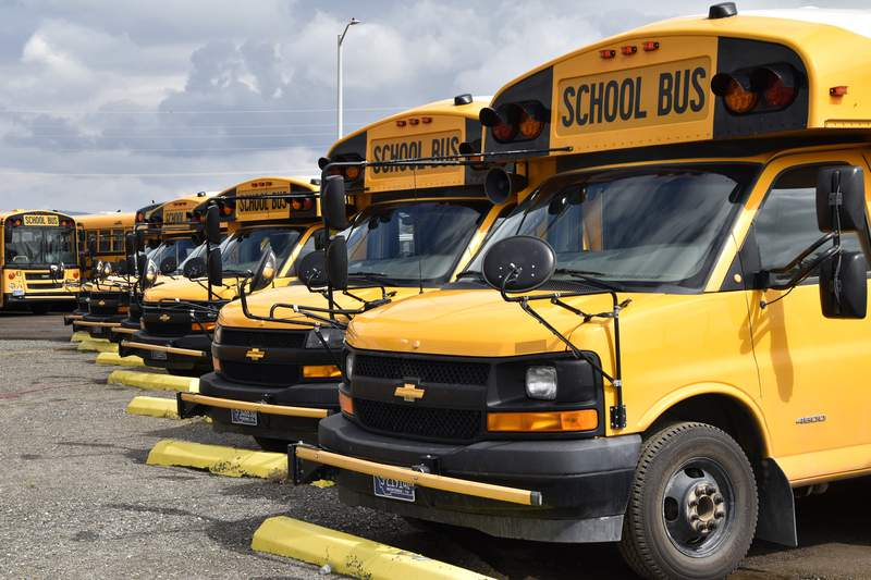 School buses parked in Helena, Mont., ahead of the beginning of the school year, Friday, Aug. 20, 2021. School districts across the country are coping with a shortage of bus drivers, a dilemma that comes even as they struggle to start a new school year during a new surge of the coronavirus pandemic.  (AP Photo/Iris Samuels)