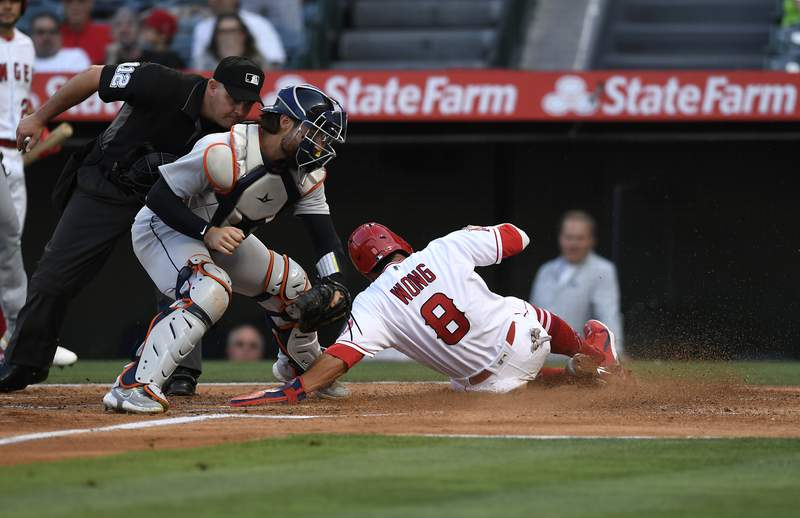ANAHEIM, CA - JUNE 17: Kean Wong #8 of the Los Angeles Angels slides under the tag of catcher Eric Haase #13 of the Detroit Tigers to score a run during the second inning at Angel Stadium of Anaheim on June 17, 2021 in Anaheim, California. (Photo by Kevork Djansezian/Getty Images)