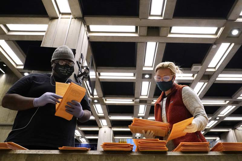 Election officials sort absentee and early voting ballots for counting inside Boston City Hall, Monday, Nov. 2, 2020, in Boston. (AP Photo/Elise Amendola)