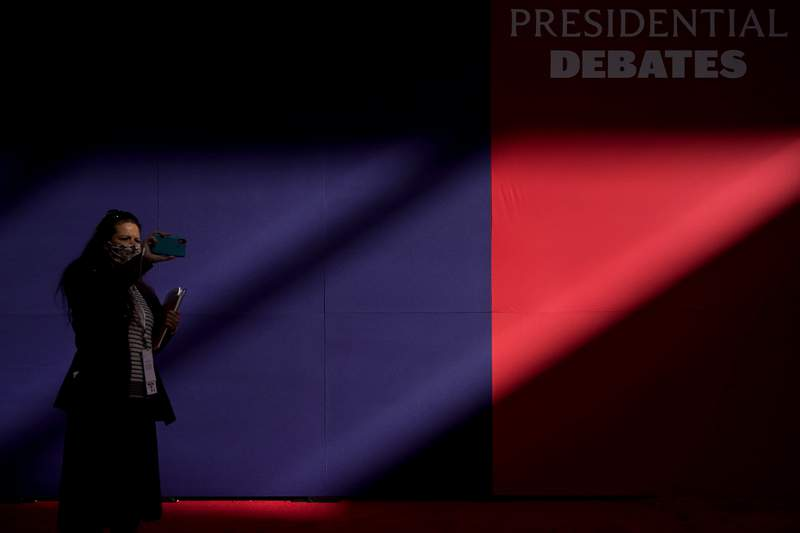 A member of the production team uses a cell phone to make images of the hall ahead of the first presidential debate between Republican candidate President Donald Trump and Democratic candidate former Vice President Joe Biden at the Health Education Campus of Case Western Reserve University, Tuesday, Sept. 29, 2020, in Cleveland. (AP Photo/Julio Cortez)