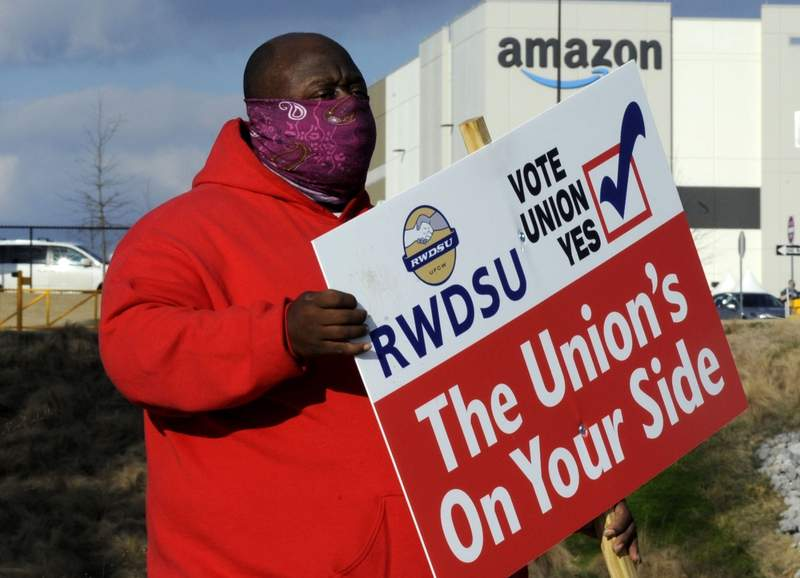 Michael Foster of the Retail, Wholesale and Department Store Union holds a sign outside an Amazon facility where labor is trying to organize workers on Tuesday, Feb. 9, 2021. President Joe Biden said workers in Alabama and across the country have the right to join a union without intimidation from their companies. His comments come as Amazon workers in the state are voting on whether they should unionize. In a two minute video posted to Twitter, Biden didnt mention Amazon by name, or say how workers should vote. (AP Photo/Jay Reeves, file)