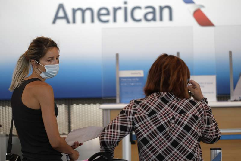 Travelers wear mask as they wait at the American Airlines ticket counter in Terminal 3 at O'Hare International Airport Tuesday, June 16, 2020, in Chicago. Beginning June 16 at American Airlines and June 18 at United Airlines, all passengers and crew members will be required to wear masks to prevent the spread of the coronavirus. (AP Photo/Nam Y. Huh)