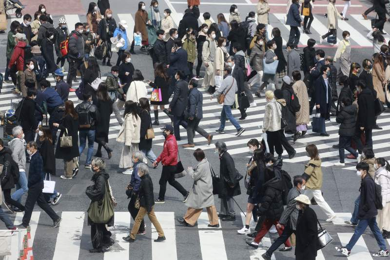 People wearing face masks to protect against the spread of the coronavirus cross a  scramble intersection in Tokyo, Tuesday, March 9, 2021. (AP Photo/Koji Sasahara)