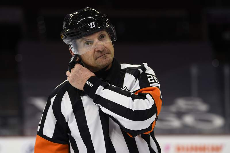 FILE - Referee Tim Peel is shown during an NHL hockey game between the Philadelphia Flyers and the New York Islanders in Philadelphia, in this Saturday, Jan. 30, 2021, file photo. Tim Peel's career as an NHL referee is over after his voice was picked up by a TV microphone saying he wanted to call a penalty against the Nashville Predators. The league on Wednesday, March 24, 2021, announced that Peel no longer will be working NHL games now or in the future. The 54-year-old Peel had already made plans to retire next month.(AP Photo/Derik Hamilton, File)