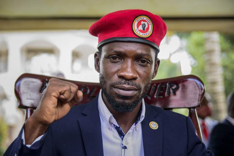 FILE - In this Tuesday, Jan. 26, 2021 file photo, opposition presidential challenger Bobi Wine, whose real name is Kyagulanyi Ssentamu, gestures as he speaks to the media outside his house after government soldiers withdrew from it, in Magere, near Kampala, in Uganda. Ugandan opposition figure Bobi Wine has been arrested Monday, March 15, 2021 while leading a protest in the capital Kampala against the detention of many of his supporters before, during and after presidential elections in January that were won by long-time leader Yoweri Museveni. (AP Photo/Nicholas Bamulanzeki, File)