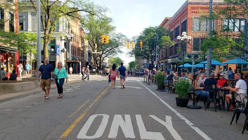Community members dine and walk around a closed Main Street in downtown Ann Arbor.