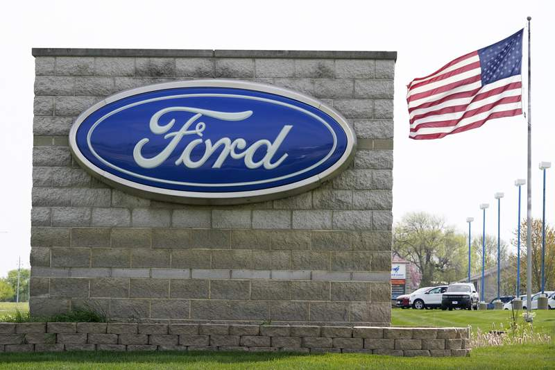FILE - In this April 27, 2021 file photo, an American flag flies over a Ford auto dealership, in Waukee, Iowa. (AP Photo/Charlie Neibergall, File)