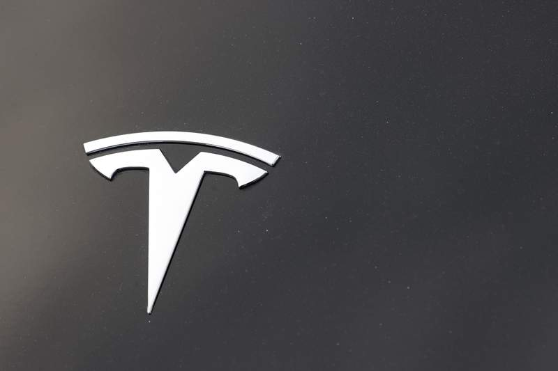 The company logo is seen on the hood of an unsold Tesla at a dealership late Sunday, Aug. 9, 2020, in Littleton, Colo. On Monday, March 15, 2021, the U.S. governments highway safety agency said it is sending a team to Detroit to investigate a crash involving a Tesla that drove beneath a semitrailer. (AP Photo/David Zalubowski)