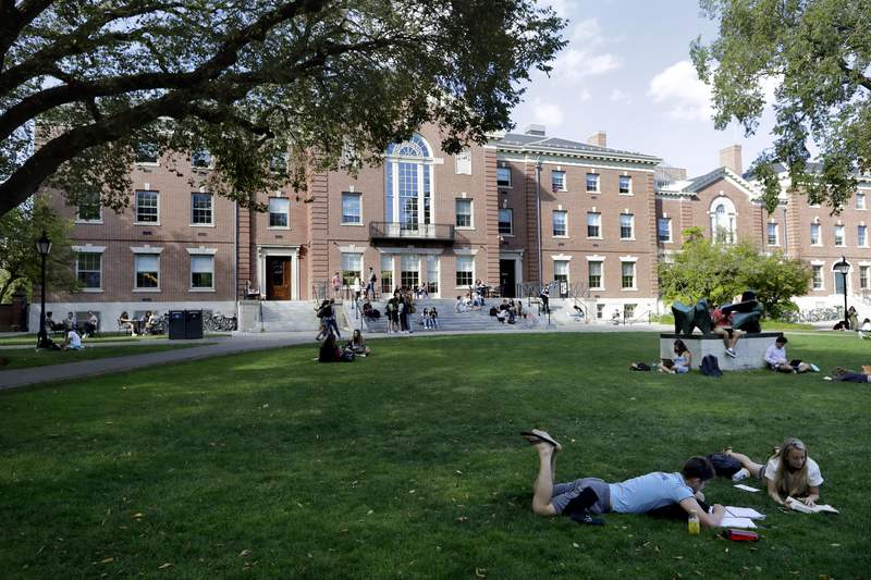 """FILE - In this Sept. 25, 2019, file photo, people rest on grass while reading at Brown University in Providence, R.I. Brown is rebutting what the Ivy League school calls """"spurious conspiracy claims"""" as it responds to an allegation that is is failing to comply with a 1998 agreement ensuring gender equity in sports. The school announced this year that it was cutting several varsity women's and men's sports and reducing them to club status. (AP Photo/Steven Senne, File)"""