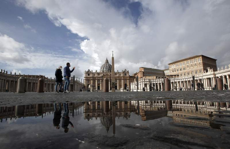 People are reflected on a puddle as they walk in an empty St.Peter's Square, as Pope Francis is reciting the Angelus noon prayer in his studio in the Apostolic palace, seen on the right, at the Vatican, Sunday, Jan. 31, 2021. (AP Photo/Alessandra Tarantino)