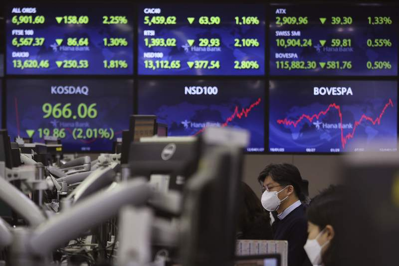 A currency trader watches monitors at the foreign exchange dealing room of the KEB Hana Bank headquarters in Seoul, South Korea, Thursday, Jan. 28, 2021. Asian shares skidded on Thursday as a reality check set in about longtime economic damage from the coronavirus pandemic, giving Wall Street its worst day since October. (AP Photo/Ahn Young-joon)