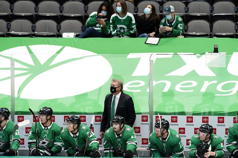 Dallas Stars coach Rick Bowness stands behind players as fans sitting a distance away watch the first period of the team's NHL hockey game against the Nashville Predators in Dallas, Friday, Jan. 22, 2021. (AP Photo/Tony Gutierrez)
