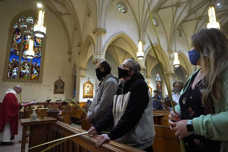 FILE - In this Sunday, March 28, 2021 file photo, the Rev. William Schipper, left, pastor of Mary, Queen of the Rosary Parish, celebrates Palm Sunday Mass as parishioners hold palm leaves at the Catholic church in Spencer, Mass. Parishioners wore masks out of concern for the coronavirus. (AP Photo/Steven Senne)