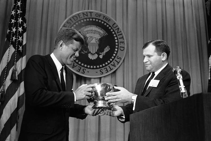 """FILE - In this March 27, 1962, file photo, President John F. Kennedy, left, receives a silver bowl from William J. Small, with station WHAS in Louisville, Ky., in a Washington ceremony. Small, representing the Radio-TV News Directors Association, presented the bowl at the conclusion of an """"off the record"""" talk by Kennedy to newsmen attending a foreign policy briefing. Longtime broadcast news executive Small, who led CBS News Washington coverage during the civil rights movement, Vietnam War and Watergate and was later president of NBC News and United Press International, died Sunday, May 24, 2020, CBS News said. He was 93. (AP Photo/File)"""