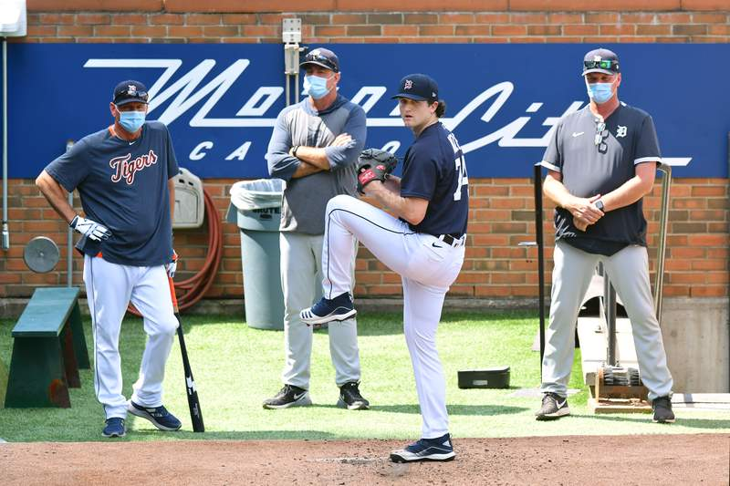 Detroit Tigers coaches look on and watch as Casey Mize #74 of the Detroit Tigers warms up in the bullpen during the Detroit Tigers Summer Workouts at Comerica Park on July 14, 2020 in Detroit, Michigan.