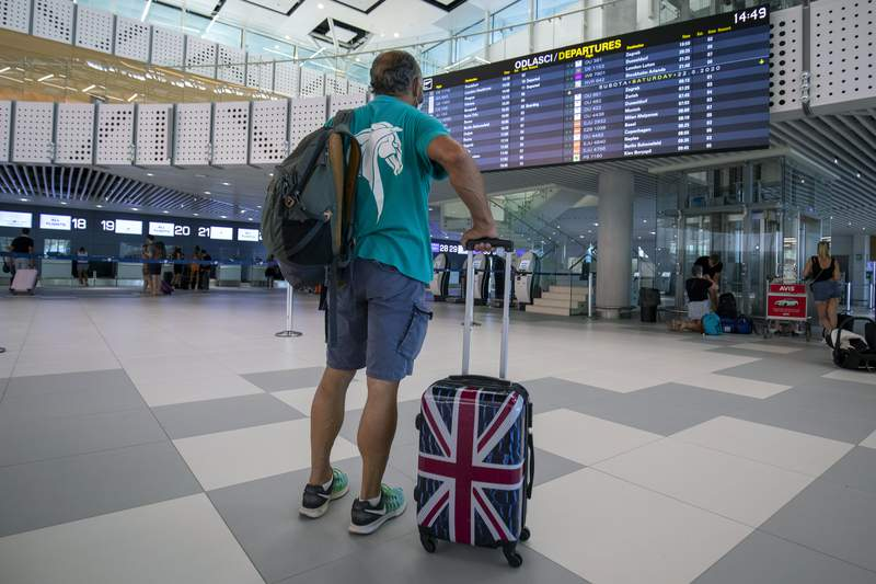 FILE - In this Friday, Aug. 21, 2021 file photo, a passenger inspects the departures timetable at the international airport in Split, Croatia. Airlines and holiday providers on Friday, June 25, 2021 expressed frustration with the U.K.s plans to ease travel restrictions, saying uncertainty about how and when the new rules will be implemented make it difficult for people to book summer vacations. (AP Photo/Miroslav Lelas, File)