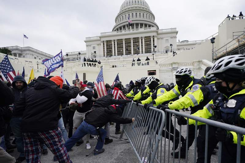 FILE - In this Wednesday, Jan. 6, 2021 file photo, Trump supporters try to break through a police barrier at the Capitol in Washington.  Right-wing extremism has previously mostly played out in isolated pockets of America or in smaller cities. In contrast, the deadly attack by rioters on the U.S. Capitol targeted the very heart of government. It brought together members of disparate groups, creating the opportunity for extremists to establish links with each other. (AP Photo/Julio Cortez, File)